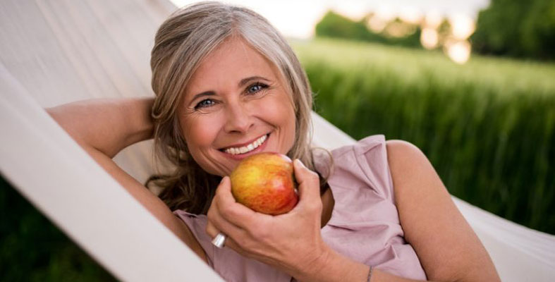 Woman Eating Apple with Dental Implants